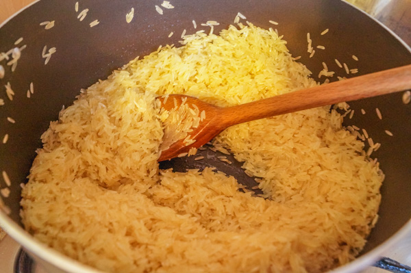 raw washed basmati rice in a pot about to be stirred.
