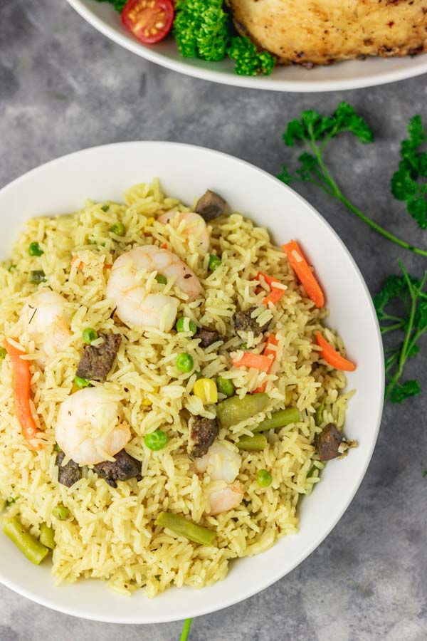 A plate of Nigerian fried rice with prawns and fried liver.
