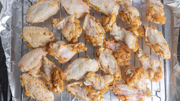 marinated chicken wings arranged on a baking tray.