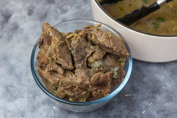 cooked meat in a glass bowl placed beside a pot.