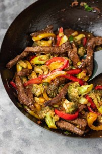 beef and broccoli stir fry in a wok.