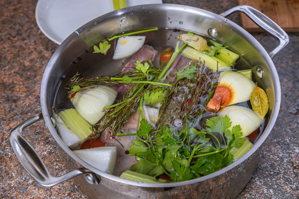 a pot filled with water and herbs.