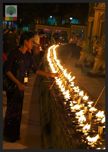 Shwedagon Pagoda by night - Worshipper Lighting Candles - Yangon - Myanmar (Burma)