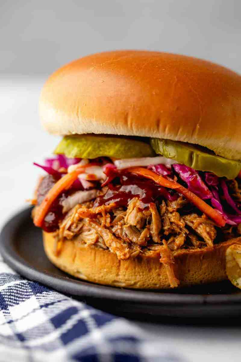 Easy Crockpot Pulled Pork is as easy as can be. Top with slaw and pickles for the perfect sandwich.