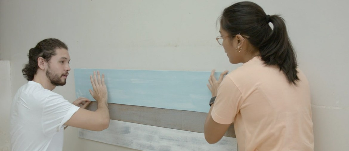 Couple putting up painted planks on the wall
