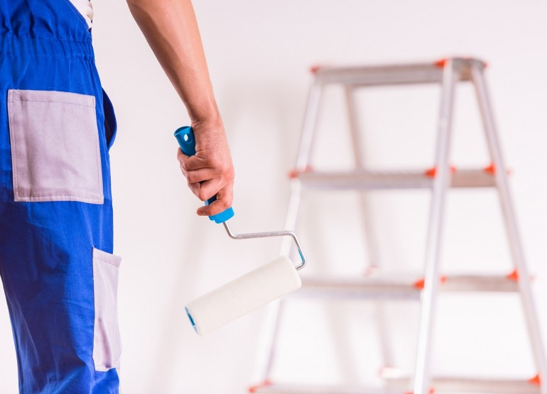 A man in overalls holding a rolling brush in front of a wall that he is about to paint