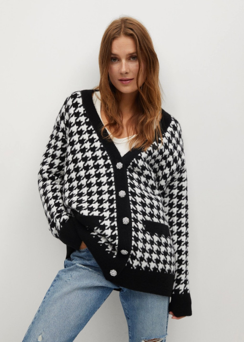 A model wearing a houndstooth cardigan in black and white with diamanté buttons, paired with jeans.