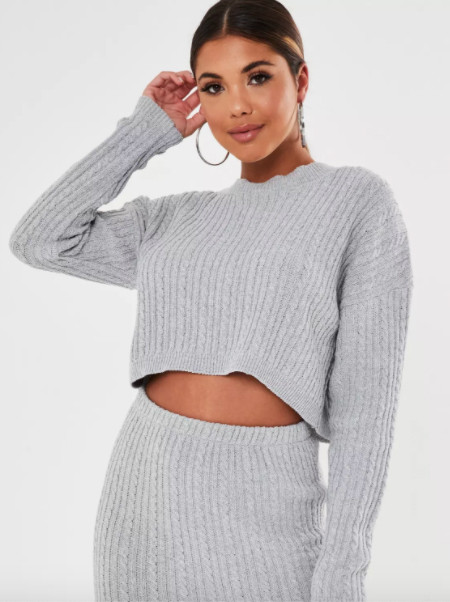 A woman wearing a grey skirt and jumper co-ords.