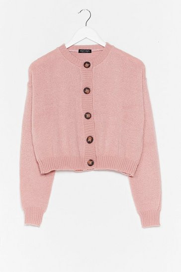 A pink cardigan on a hanger