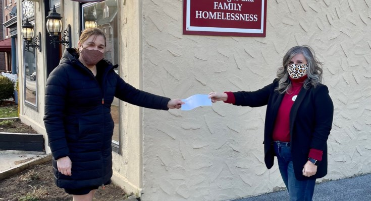 Amy Brooks Presents Check to Emily McClure of Friends Assn