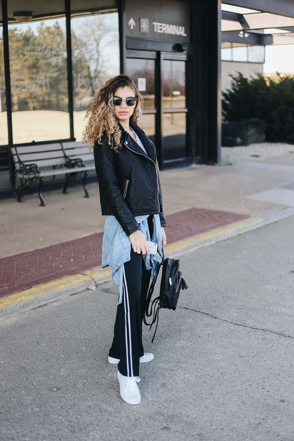 comfy airport outfit with track pants and a motorcycle jacket