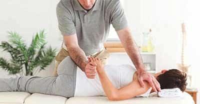 Chiropractor treating lumbar spine of female