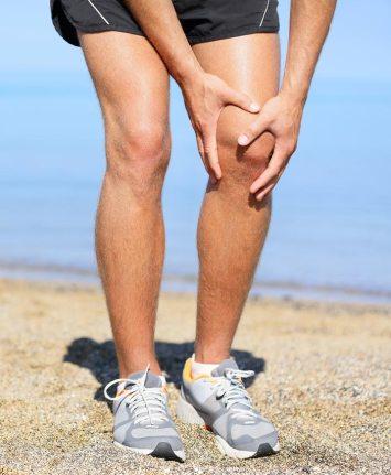 knee pain, man holding knee in pain