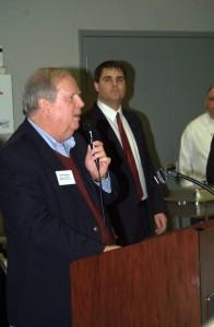 Mayor Bob Mezzo (right) watches Dave Prendergast, CEO of the NEDC, address local business representatives.