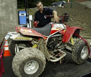 Former Naugatuck police officer David Reilly, pictured in 2004 filling the gas tank of an ATV used to patrol illegal ATV and dirtbike riding, has resigned from the NPD. Though he faces multiple felony charges, he claims his resignation is due to a disability and is requesting a pension.