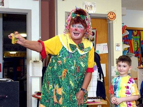Sparkles the Clown, left, holds up a box of crayons for Joey Spina to color in her magic coloring book.