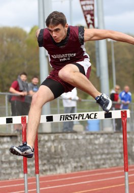 Naugatuck's Colton Wagner clears a hurdle during Naugatuck's home track meet May 5. - PHOTO BY LARAINE WESCHLER
