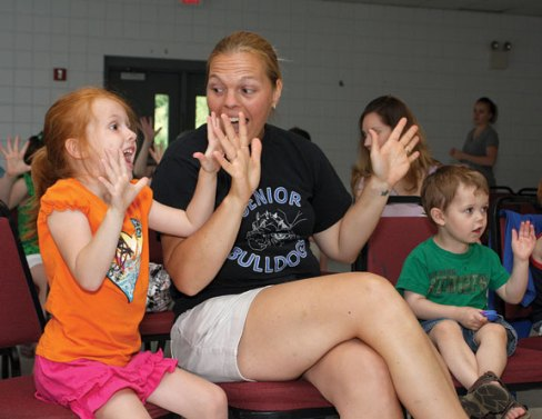 Paige Kavanaugh, 5, left, and Aryn Kavanaugh participate in Les Julian's children's concert, We All Laugh in the Same Language, July 7 at the Prospect Fire House. The concert was hosted by the Prospect Public Library.