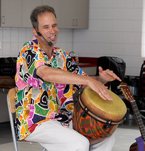 Les Julian finds his rhythm on the djembe during his children's concert, We All Laugh in the Same Language, July 7 at the Prospect Fire House. The concert was hosted by the Prospect Public Library.