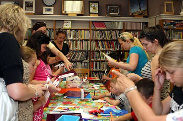 Parents and their children decorate masks July 14 as part of a children's program at the Beacon Falls Library.