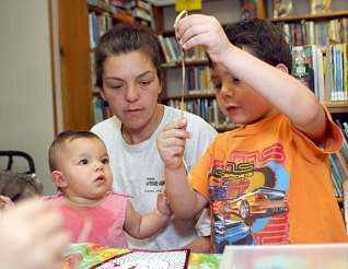 Alivia Ruggiano, 9 months, helps her older brother, Robbie Ruggiano, 5, decorate a mask as their mother, Sarah Ruggiano, watches over July 14 at the Beacon Falls Public Library.