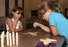"""Shaylin Fisher, 7, left, and Juliana Sarbieski, 7 play pick up sticks during a children's program, """"Yesterday's Toys and Games,"""" at the Naugatuck Historical Society Aug. 5."""