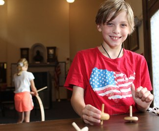 """Johnathan McPhail, 9, plays with spinning tops during a children's program, """"Yesterday's Toys and Games,"""" at the Naugatuck Historical Society Aug. 5."""