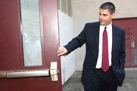 Mayor Robert Mezzo looks at a rusty door handle at the entrance to the Naugatuck High School pool during a tour of the high school Aug. 25.
