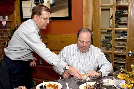 "Naugatuck Valley Savings and Loan CEO John Roman serves employee Mark Graveline during the ""Waiters go Pink"" fundraiser at Jesse Camilles Restaurant Monday night."