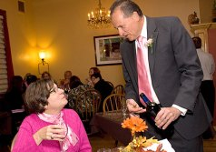 """Naugatuck Savings Bank President and CFO Chuck Boulier pours wine for Linda Zibluk from Griffin Hospital during the """"Waiters go Pink"""" fundraiser at Jesse Camilles Restaurant Monday night."""