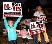 From left, Jordyn Hunt, 9, Sydney Hunt, 6, Taylor Hunt, 11, and Jim Goggin support a 'yes' vote on the Naugatuck High School renovation referendum outside the Naugatuck Train Station Tuesday evening. The referendum passed 1,756 to 944.