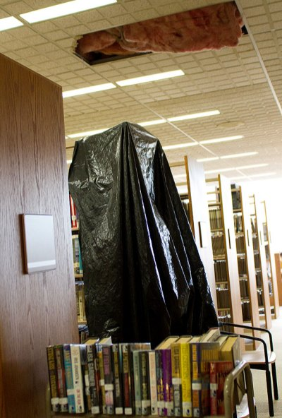 A shelf of books is covered with plastic to prevent water leaking from the ceiling to inundate books at the Whittemore Library.