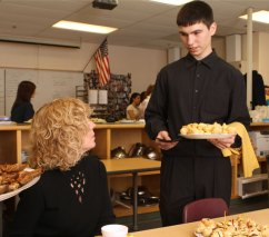 Junior James Barrett, right, serves his mother Sue Barrett hors d'oeuvres for a culinary class at Woodland Regional High School Monday morning.