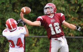 Naugatuck's Zac Mercer (12) hauls in a 35-yard pass over Derby's Brian Dobck (34) Sept. 24 at Municipal Stadium in Waterbury. The Greyhounds earned a hard-fought 14-13 win. -RA ARCHIVE