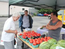 Clem Cardow, left, of Beacon Falls looks over some fresh vegetables from Sunflower Farms in Cheshire as she talks with Martha Berge, an EMT from Beacon Hose Company No. 1, and Joe Sanpieri of Sunflower Farms during the Beacon Falls Farmers Market's opening day July 20 next to the firehouse on North Main Street in Beacon Falls. This year is the first year the town has held a farmers market. Economic Development Commission Chair Jeremy Rodorigo explained the market was the result of a suggestion a resident made to the commission last year. Last Friday, Beacon Hose Company No. 1 was selling baked goods and Sunflower Farmers was selling vegetables and fruits. Rodorigo said he has received calls from six vendors interested in participating in the market. 'We're hoping that it'll keep growing,' Rodorigo said. The market is open every Friday from 3 to 6 p.m. until the end of October on North Main Street. –ELIO GUGLIOTTI