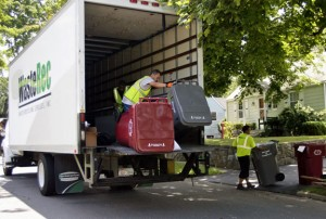 Workers deliver 96-gallon carts for trash and recycling barrels to Naugatuck homes in the summer of 2012. The borough has seen an increase in recycling figures as well as savings now that all homes have the larger bins for recycling. –RA ARCHIVE