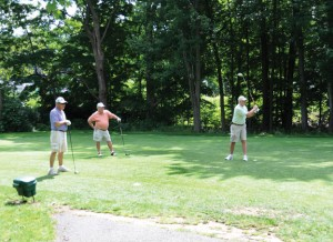 Michael Bogis tees off at Hop Brook Golf Course in Naugatuck last summer while Mario Pannone, left, and Dave Pendergast look on. The course is running a deficit, leading officials to debate whether the borough should subsidize it anymore. –FILE PHOTO