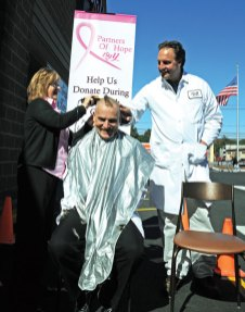 Naugatuck Big Y customer service manger Dave Mals gets his head shaved by head cashier Karen Sabia on Saturday while store director Jim Martin looks on. The pair shaved their heads to reward the store's staff for raising the most money in the district selling pink ribbons for the St. Mary's Breast Oncology Center. The store raised $3,618. –LUKE MARSHALL