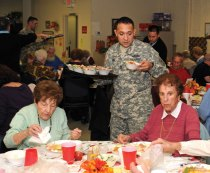 Army Sgt. First Class Miguel Diaz from the Recruiting Command in Waterbury serves food to seniors during the Naugatuck Senior Center's Apple Festival Oct. 18. -LUKE MARSHALL