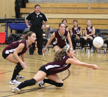 Naugatuck's Melissa Ascencao dives for a dig in front of teammate Raquel Loustanau Oct. 5 versus Woodland in Beacon Falls. The Hawks won the match in three sets (25-17, 25-21, 25-20). –ELIO GUGLIOTTI