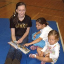 Jaimie Cormier, a member of the Woodland Regional High School dance team, reads with a couple of youngsters during Laurel Ledge Family Reading Night recently. Laurel Ledge students read their favorite books with athletes from Woodland during the event. –CONTRIBUTED