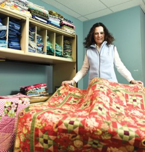 Deborah Van Steenbergen fluffs a quilt inside her new warehouse space in Naugatuck.  Steenbergen, of Watertown, is the founder of Quilts That Care, which brings volunteers together to make quilts for cancer patients in treatment. She says the idea is to let them know that they aren't alone. -RA ARCHIVE