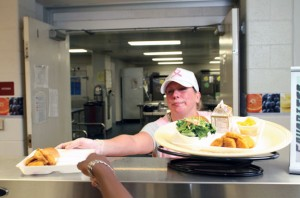 Maggie Bradshaw serves up chicken nuggets last fall in Naugatuck High School. The food services in Naugatuck public schools recently aced a surprise audit. –RA ARCHIVE