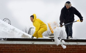 Eric Figueroa and Jonathan Morreno of Green Construction work to shovel a 5-foot snowdrift from the top of Community School in Prospect Monday. Schools in Naugatuck and Region 16, which serves Prospect and Beacon Falls, have been closed since Friday when a blizzard dumped about 3 feet of snow in the area. –RA ARCHIVE