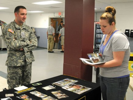Naugatuck High School junior Ashley Shaw looks over a pamphlet about the U.S. Army and talks with Sgt. Curtiss Leilich April 9 during college fair for juniors and seniors at the school. –LUKE MARSHALL
