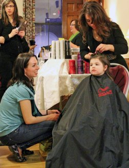Young Aubrey Marino of Naugatuck gets her hair braided by Lori Turiano, owner of The Pendulum Salon in Southbury, as her mother, Jessica Marino, looks on during the Girls Night Out April 5 at the Naugatuck Congregational Church. The event was hosted by Tender Years Preschool and raised $1,800 for the Dawn Lafferty Hochsprung Memorial Fund. –ELIO GUGLIOTTI