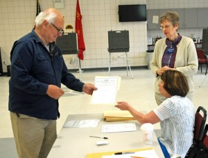 Prospect resident Alexander Delelle, left, receives a ballot to vote on the proposed $7.4 million town budget from volunteer Kathleen Graveline while Deputy Registrar of Voters Betty Guevin looks on Monday at the Volunteer Firehouse of Prospect. The budget failed by 66 votes. –LUKE MARSHALL