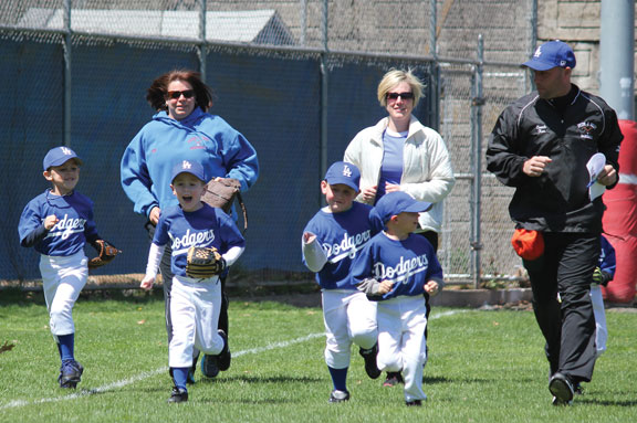 Players run to the infield during Peter J. Foley Little League's opening day ceremony last April. The league has announced registration dates for the 2014 season. –FILE PHOTO