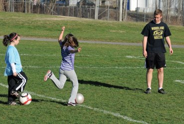 Woodland Regional High School senior Mike Costa instructs children how to shoot a soccer ball April 18. Costa and fellow senior Steph Dumond hosted a week-long soccer camp for children ages 5 to 10 during the school's April vacation as their senior projects. 'We decided to choose soccer since both of us have been playing since we were 4-years-old ourselves, so we know what it's like to look up to the kids who are playing high school soccer,' Costa said. –LUKE MARSHALL