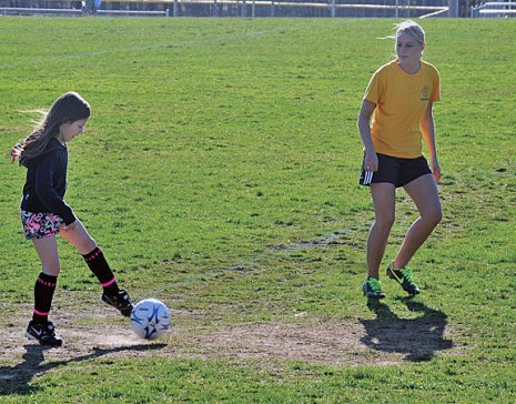 Woodland Regional High School senior Steph Dumond instructs children how to shoot a soccer ball April 18. Dumond and fellow senior Mike Costa hosted a week-long soccer camp for children ages 5 to 10 during the school's April vacation as their senior projects. 'We're just trying to teach the kids what we know,' Dumond said. –LUKE MARSHALL